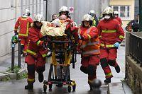 dpatopbilder - 25.09.2020, Frankreich, Paris: Einsatzkr�fte der Feuerwehr schieben eine Trage mit einem Verletzten. Bei einer Messerattacke sind mindestens vier Menschen verletzt worden. Der Vorfall ereignete sich am Freitagmittag in der N�he der ehemaligen Redaktionsr�ume des Satiremagazins �Charlie Hebdo� Foto: Alain Jocard/AFP/dpa +++ dpa-Bildfunk +++