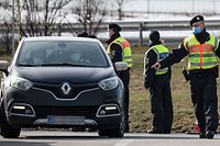Officers of the Federal Police control a German car at the German-Czech border in an attempt to stem the spread of the new coronavirus variants, in Breitenau, eastern Germany, on February 18, 2021. - Germany partially closed its borders with the Czech Republic and Austria's Tyrol on February 14 over a troubling surge in coronavirus mutations, defying condemnation from the European Union. Germany's new rules on its borders mean only German nationals or residents of Germany are allowed through. Essential workers in sectors such as health and transport can also enter, as well as those crossing for urgent humanitarian reasons, according to the German interior ministry. Everyone must be able to provide a recent negative coronavirus test. (Photo by JENS SCHLUETER / AFP)