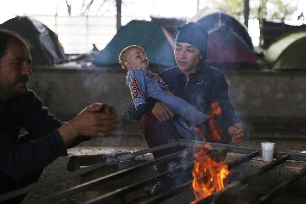 Eine Familie in Idomeni wärmt sich am Feuer.