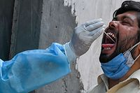 A medical worker takes a swab sample from a man for a Reverse Transcription Polymerase Chain Reaction (RT-PCR) test at a testing centre in Ghaziabad on April 28, 2021. (Photo by Prakash SINGH / AFP)