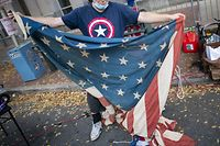 PHILADELPHIA, PA - NOVEMBER 10: Dana Benson, 63, a supporter of President Donald Trump unfurls a U.S. flag while demonstrating outside of where votes are still being counted in Pennsylvania, seven days after the general election on November 10, 2020 in Philadelphia, Pennsylvania. The state was called for President-elect Joe Biden on Saturday, propelling him past the requisite 270 electoral votes to win the presidency. As of Tuesday afternoon, with 98% of the ballots reported, President-elect Biden leads President Trump in the state by 45,103 votes.   Mark Makela/Getty Images/AFP == FOR NEWSPAPERS, INTERNET, TELCOS & TELEVISION USE ONLY ==