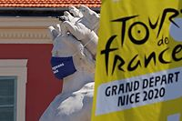 The logo of the 2020 Tour de France is seen next to a masked statue in the French Riviera city of Nice on August 26, 2020. - The 2020 edition of the Tour de France kicks off in Nice on August 29 and runs to September 20, postponed from June 27 to July 19 due to the coronavirus pandemic. (Photo by Kenzo Tribouillard / AFP)