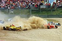 German Ferrari driver Michael Schumacher (C) runs into the sand after colliding with his brother Ralf on Jordan-Peugeot (L) on the first curve after the start of the Luxembourg Formula One Grand Prix, 28 September, on the Nurburgring racetrack. Both had to abandon the race. / AFP PHOTO / UTA TOCHTERMANN