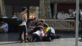 """People help injured persons after a van ploughed into the crowd, killing at least 13 people and injuring around 100 others on the Rambla in Barcelona on August 17, 2017. A driver deliberately rammed a van into a crowd on Barcelona's most popular street on August 17, 2017 killing at least 13 people before fleeing to a nearby bar, police said.  Officers in Spain's second-largest city said the ramming on Las Ramblas was a """"terrorist attack"""". The driver of a van that mowed into a packed street in Barcelona is still on the run, Spanish police said. / AFP PHOTO / NICOLAS CARVALHO OCHOA"""