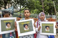 (FILES) In this file photo taken on April 12, 2019 women hold placards with a photograph of schoolgirl Nusrat Jahan Rafi at a protest in Dhaka, following her murder by being set on fire after she had reported a sexual assault. - A court in Bangladesh sentenced 16 people to death on October 24 over the murder of a 19-year-old female student burnt alive in April that provoked outrage across the country. (Photo by SAZZAD HOSSAIN / AFP)