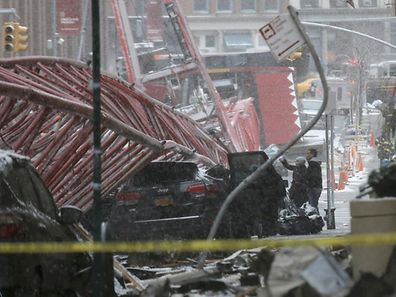 Emergency crews survey a massive construction crane collapse on a street in downtown Manhattan in New York, February 5, 2016.  The accident killed at least one person and seriously injuring two others, a spokesman for the New York City Fire Department said.   REUTERS/Brendan McDermid
