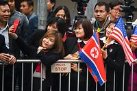 A woman takes a selfie as people gather around a street in Hanoi on February 26, 2019, ahead the second US-North Korea summit. - North Korean leader Kim Jong Un crossed into Vietnam on February 26 after a marathon train journey for a second summit showdown with Donald Trump, with the world looking for concrete progress over the North's nuclear programme. (Photo by Noel CELIS / AFP)