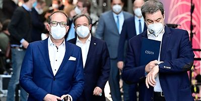 Markus Soeder (right) checks his watch as he leaves a press conference with Armin Laschet (back centre) and Christian Social Union (CSU) parliamentary group leader Alexander Dobrindt (left) in Berlin on Sunday