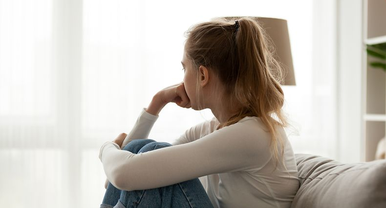 Side view young woman looking away at window sitting on couch at home. Frustrated confused female feels unhappy problem in personal life quarrel break up with boyfriend or unexpected