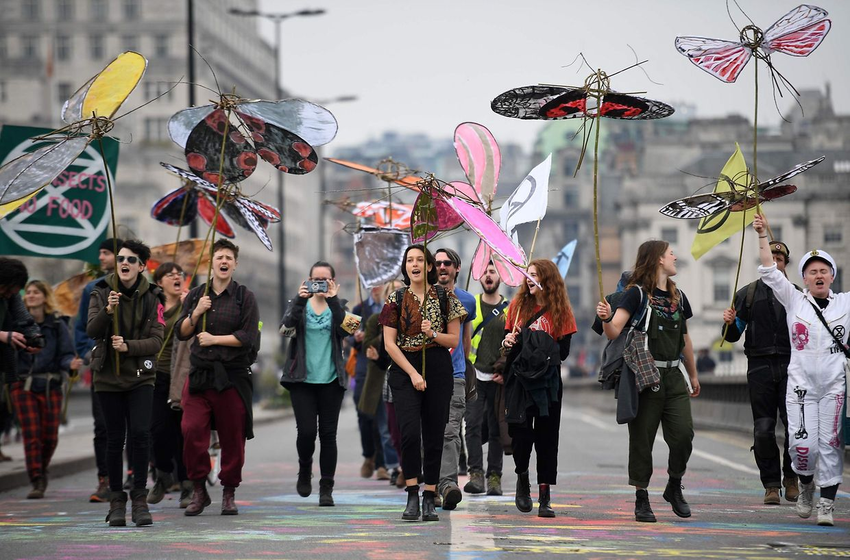 "Activists hold model insects as the demonstrate on Waterloo Bridge on the second day of an environmental protest by the Extinction Rebellion group, in London on April 16, 2019. - Environmental protesters from the Extinction Rebellion campaign group started a programme of demonstrations designed to block five of London's busiest and iconic locations to draw attention to what they see as the ""Ecological and Climate Emergency"" of climate change. (Photo by Daniel LEAL-OLIVAS / AFP)"