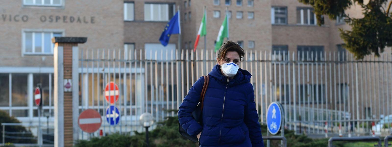 Eine Krankenschwester mit Grippeschutzmaske geht aus dem Krankenhaus der Stadt Codogno in der Lombardei. Etwa 50.000 Menschen in der Region wird empfohlen, wegen des Virus möglichst nicht außer Haus zu gehen.