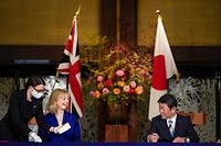 British Secretary of State for International Trade Elizabeth Truss (2nd L) and Japanese Foreign Minister Toshimitsu Motegi (R) take part in a signing ceremony for economic partnership between Japan and Britain at the Iikura Annex of the Foreign Ministry in Tokyo on October 23, 2020. (Photo by Kimimasa MAYAMA / POOL / AFP)