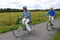dpatopbilder - 27.06.2020, Belgien, Genk: Königin Mathilde von Belgien und König Philippe von Belgien radeln während einer Fahrradtour im Rahmen eines Familienausflugs im Bokrijk-Park und Freilichtmuseum - beide tragen einen Fahrradhelm. Foto: Dirk Waem/BELGA/dpa +++ dpa-Bildfunk +++