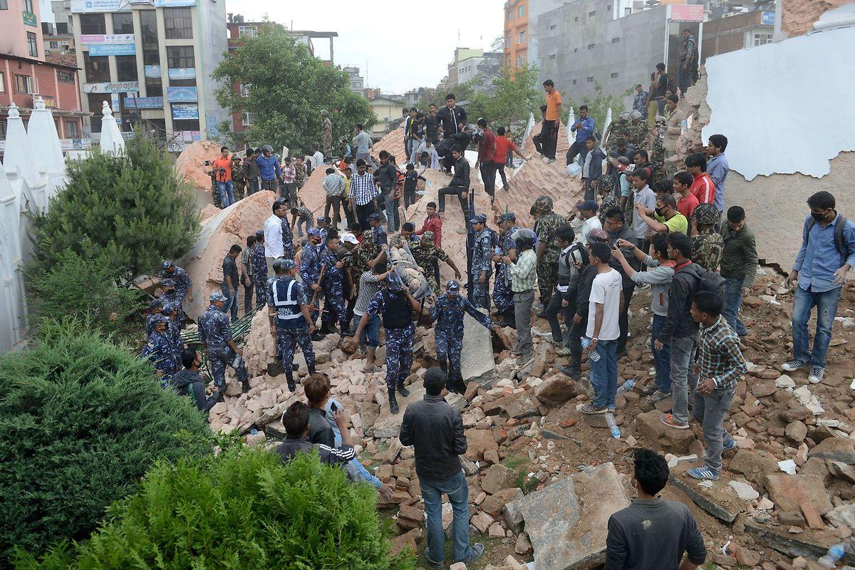 Des sauveteurs népalais éloignent le corps d'une victime de l'effondrement de la tour Dharahara