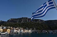 This picture shows a view of the tiny Greek island of Kastellorizo (Megisti) with a Greek flag, in the Dodecanese, the furthest south eastern Greek Island, two kilometers from the Turkish mainland, on August 28, 2020. (Photo by Louisa GOULIAMAKI / AFP)