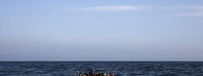 Un hélicoptère de Frontex vole au-dessus d'un bateau à bord duquel se trouvent des migrants près de l'île de Lesbos, en Grèce, le 8 novembre 2015.
