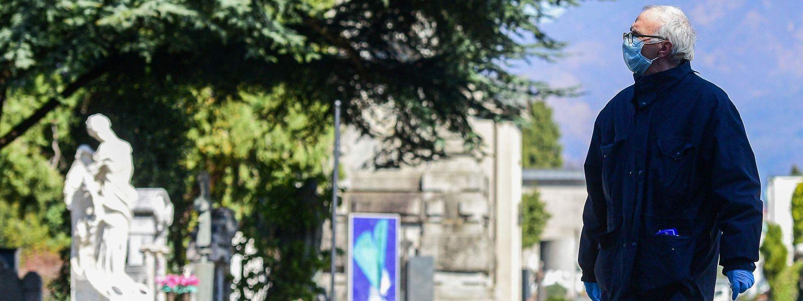 Ein Totengräber mit Mundschutz und Einmalhandschuhen am Friedhof Monumentale in Bergamo.