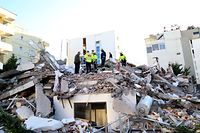Emergency workers look for survivors trough the rubble of a building in the coastal city of Durres, west of capital Tirana following an earthquake, on November 26, 2019. - Albanian rescuers dug through rubble as desperate survivors trapped in toppled buildings cried out for help Tuesday after the strongest earthquake in decades killed at least 16 people and left hundreds injured. The 6.4 magnitude quake struck before dawn at 3:54 am local time (0254 GMT), with an epicentre 34 kilometres (about 20 miles) northwest of the capital Tirana, according to the European-Mediterranean Seismological Centre. (Photo by Gent SHKULLAKU / AFP)