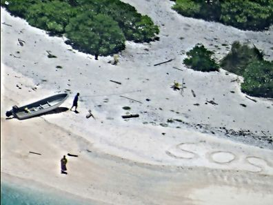 "This image obtained courtesy of the US Navy shows a pair of stranded mariners signal for help by writing ""SOS"" in the sand"