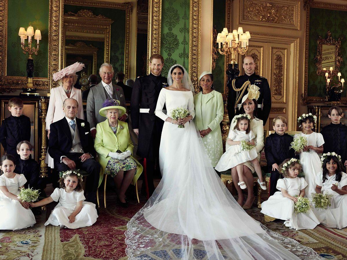 Das offizielle Hochzeitsfoto zeigt Prinz Harry, Herzog von Sussex (Mitte links), und seine Ehefrau Meghan, Herzogin von Sussex (Mitte rechts), zusammen mit ihren Angehörigen (stehend von links nach rechts): Camilla, Herzogin von Cornwall, Prinz Charles, Prinz von Wales, Doria Ragland, die Brautmutter, Prinz William, Herzog von Cambridge (sitzend von links nach rechts): Jasper Dyer, Prinz Philip, Herzog von Edinburgh, Königin Elizabeth II., Catherine, Herzogin von Cambridge, Prinzessin Charlotte von Cambridge, Prinz George von Cambridge sowie die Brautkinder Rylan Litt, John Mulroney und (vorne) Ivy Mulroney, Brian Mulroney, Florence van Cutsem, Zalie Warren und Remi Litt.