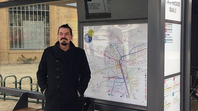 Jug Cerovic stands in front of the Luxembourg City bus map, which he designed