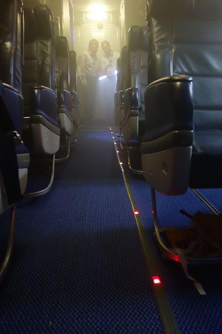 Rauch in der Kabine einer Boeing 737: Lichter im Boden zeigen den Weg zum nächsten Ausgang.