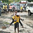 "TOPSHOT - Haitian people cross the river La Digue in Petit Goave where the bridge collapsed during the rains from Hurricane Matthew, southwest of Port-au-Prince, October 6, 2016.  Hurricane Matthew has left at least 23 people dead in Haiti, a toll likely to climb as authorities re-establish contact with the hardest-hit areas where the damage is ""catastrophic,"" officials said. The Caribbean's worst storm in nearly a decade, Matthew slammed into Haiti, the Americas' poorest nation, with heavy rains and devastating winds triggering severe flooding and mud slides.  / AFP PHOTO / HECTOR RETAMAL"