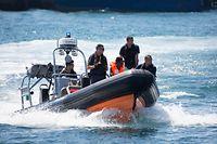 20.08.2019, Italien, Lampedusa: Beamte der Guardia di Financa bringen einen Geflüchteten in den Hafen von Lampedusa. Insgesamt neun Geflüchtete hatten versucht, vom Schiff Open Arms an Land zu schwimmen und wurden von der Küstenwache und der Guardia Financa gerettet. Foto: Friedrich Bungert/-/dpa - ACHTUNG: Nur zur redaktionellen Verwendung im Zusammenhang mit der aktuellen Berichterstattung und nur mit vollständiger Nennung des vorstehenden Credits +++ dpa-Bildfunk +++