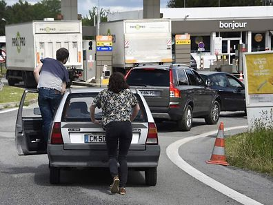 People push their car to save oil before refueling at a gas station following the blockades of oil depot during protest against proposed government labour and employment law reforms in Vern-sur-Seiche, suburb of the western city of Rennes on May 23, 2016. Petrol shortages caused long tailbacks of motorists in parts of France on May 23, 2016, as protesters angry over government labour reforms blockaded some of the country's oil refineries and fuel depots. / AFP PHOTO / DAMIEN MEYER