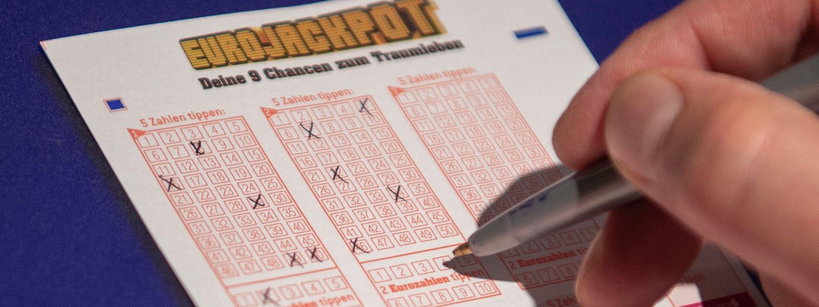 """Ein Mann kreuzt auf einem Lottoschein des Spiels """"Eurojackpot"""" Zahlen an."""