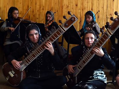 In this photograph taken on January 8, 2017, Afghan music students play during a rehearsal at The Afghanistan National Institute of Music in Kabul. In the face of death threats and accusations they are dishonouring their families by daring to perform, the women of Afghanistan's first all-female orchestra are  charting a new destiny for themselves through music. The group is set to be catapulted onto the world stage with a performance at the World Economic Forum in Davos.  / AFP PHOTO / WAKIL KOHSAR / To go with 'Afghanistan-Music-Gender-Davos-Social' by Anne CHAON