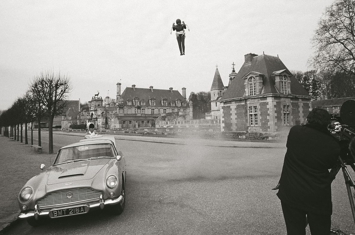 """Szene aus """"Feuerball"""" (1965) mit Sean Connery: Die französische Spionin Mademoiselle Laporte wartet am Aston Martin DB5 auf James Bond, der gerade mit einem Raketenrucksack landet."""
