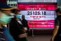 Pedestrians walk past an electronic sign displaying the Hang Seng Index in Hong Kong on March 9, 2020. - Hong Kong stocks ended Monday's morning session sharply lower, in line with a rout across Asia, on coronavirus fears, while energy firms were battered by a crash in oil prices. (Photo by ISAAC LAWRENCE / AFP)