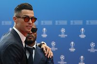 TOPSHOT - Portuguese forward Cristiano Ronaldo (L) greets retired French defender Patrice Evra as he arrives prior to the UEFA Champions League football group stage draw ceremony in Monaco on August 29, 2019. (Photo by Valery HACHE / AFP)