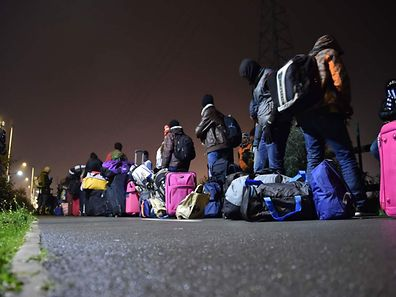 """Migrants queue for transportation by bus to reception centres across France, from the """"Jungle"""" migrant camp in Calais, northern France, on October 24, 2016. French authorities are set to begin on October 24, 2016 moving thousands of people out of the notorious Calais Jungle before demolishing the camp that has served as a launchpad for attempts to sneak into Britain. A major three-day operation is planned to clear the sprawling shanty town near Calais port -- a symbol of Europe's failure to resolve its migrant crisis -- of its estimated 6,000-8,000 occupants. The current Jungle camp dates from April 2015 and housed more than 10,000 migrants at its peak, although that number has dwindled to around 5,000 in its final days. / AFP PHOTO / PHILIPPE HUGUEN"""