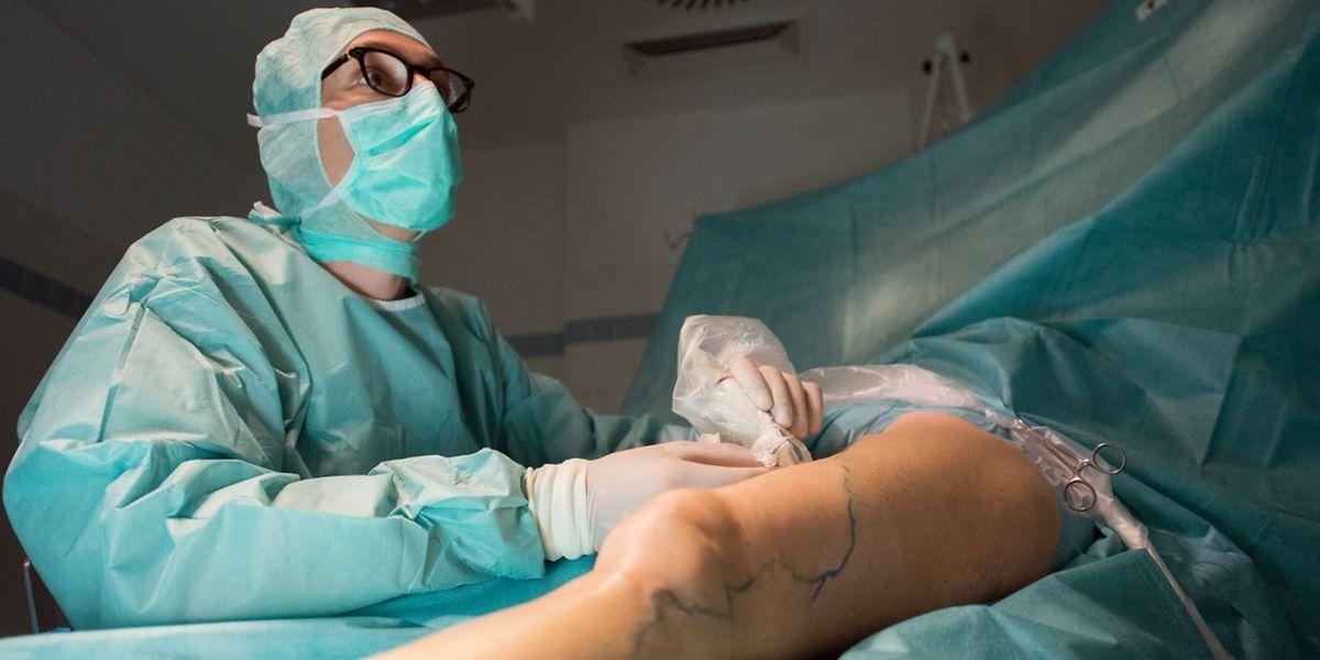 Vor der anstehenden Laserbehandlung der Krampfader punktiert ein Arzt unter Ultraschallkontrolle die Beinvene einer Patientin.