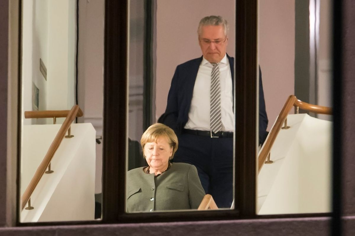 German Chancellor and leader of the Christian Democratic Union (CDU) party, Angela Merkel (L) and Interior Minister of the State of Bavaria Joachim Herrmann are seen coming down a staircase duringa break in exploratory talks to form a new government on November 17, 2017