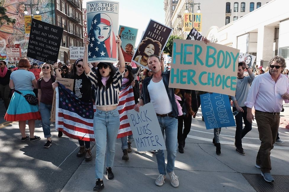 """Marchers hold signs during the Women's March on January 21, 2017 in Los Angeles, California. The """"Mexico City Policy"""" has been instituted by every Republican President since 1984."""