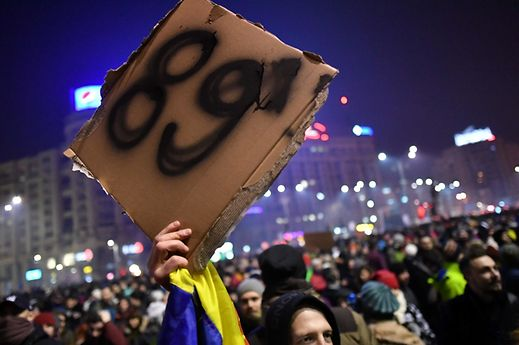 "A man holds a placard reading ""'89"" , the year of the Romanian Revolution from 1989 which toppled late dictator Nicolae Ceausescu as people demonstrate in front of Romanian Government headquarters"