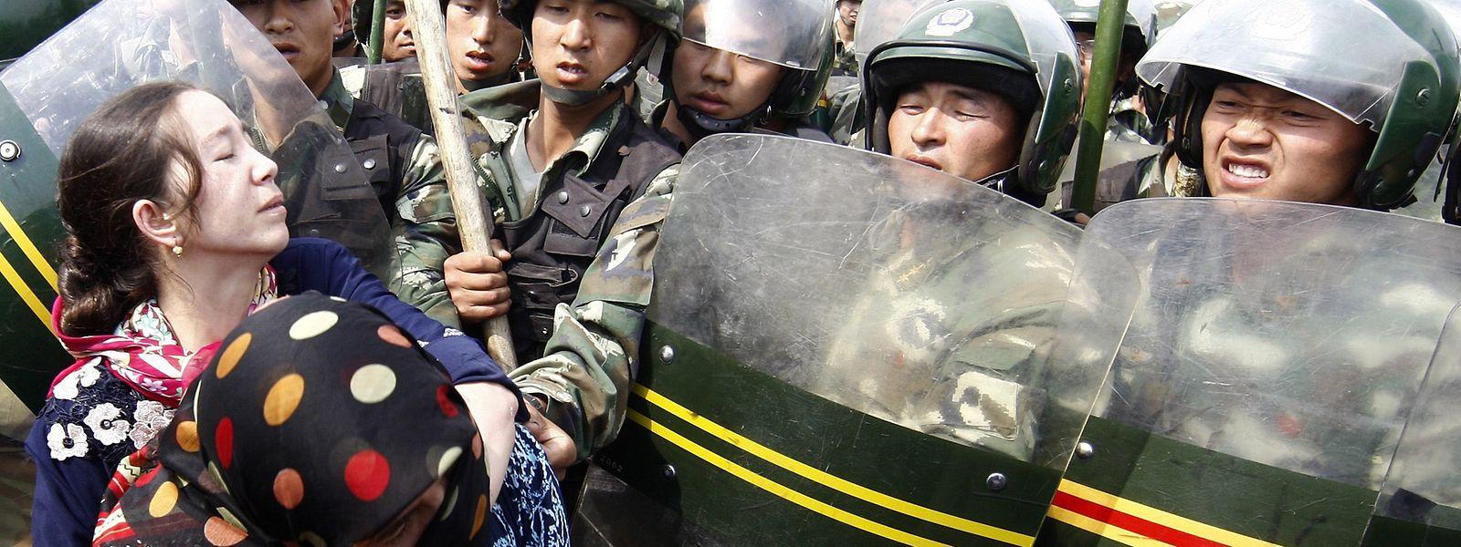 China, Ürümqi: Demonstranten wehren sich gegen einen Polizeieinsatz.