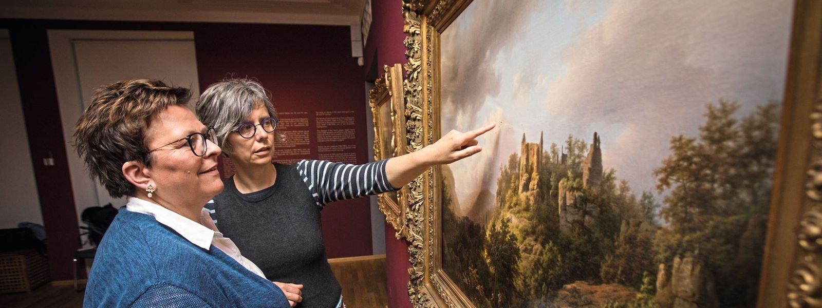 """Das Gemälde """"Luxemburgische Landschaft mit Burgruine Fels (Larochette)"""" von Barend Cornelis Koekkoek aus dem Jahr 1848 ist der Epoche der Romantik zuzuordnen. Die beiden Restauratorinnen vom MNHA, Simone Habaru (links) und Muriel Prieur, waren ein Jahr lang damit beschäftigt, das Bild wieder auf Vordermann zu bringen."""