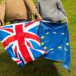 People display United Kingdom and Europe's flags on June 24, 2016 in Neufch�tel-Hardelot. Brexit campaigner Michael Gove announced a surprise bid Thursday to become Britain's next prime minister, in a blow for his close ally Boris Johnson's chances, as turmoil gripped both the country's main political parties after the shock vote to leave the EU. / AFP PHOTO / PHILIPPE HUGUEN