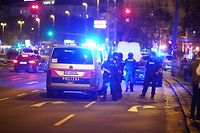 """Police cars and armed police offficer stand in central Vienna on November 2, 2020, following a shooting near a synagogue. - Multiple gunshots were fired in central Vienna on the evening of November 2, 2020, according to police, with the location of the incident close to a major synagogue. Police urged residents to keep away from all public places or public transport. One attacker was """"dead"""" and another """"on the run"""", with one police officer being seriously injured, Austria's interior ministry said according to news agency APA. (Photo by GEORG HOCHMUTH / APA / AFP) / Austria OUT"""