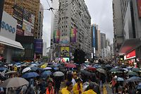 People gather for a rainy protest march in the Causeway Bay shopping district of Hong Kong on October 6, 2019. - A Hong Kong judge on October 6 rejected a challenge to an emergency law criminalising protesters wearing face masks as democracy activists hit the streets again in defiance of the ban despite half the city's subway stations remaining closed. (Photo by Nicolas ASFOURI / AFP)