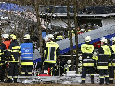 Members of emergency services work at the site of the two crashed trains near Bad Aibling in southwestern Germany, February 9, 2016. Several people died after two trains collided in the southern German state of Bavaria on Tuesday, a police spokesman said, adding about 100 people were also injured.   REUTERS/Michael Dalder