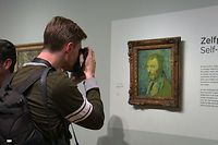 "This video grab image shows a photographer taking a close up of a self-portrait by Dutch artist Vincent van Gogh on display at The Van Gogh Museum in Amsterdam on January 20, 2020, after it was declared as genuine. - A gloomy self-portrait by Vincent van Gogh was declared genuine after decades of uncertainty, experts identifying it as the only work painted by the Dutch master while he suffered from psychosis. The ""Self Portrait (1889)"" -- which shows the artist giving a haunted sideways glance against a swirling blue and yellow background -- was confirmed as authentic by the Van Gogh Museum in Amsterdam. (Photo by Sara MAGNIETTE / various sources / AFP)"