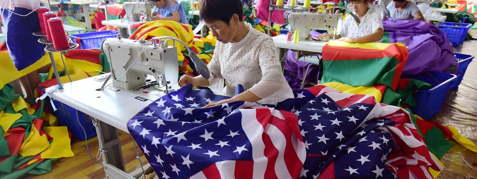 Cette photo prise le 13 juillet montre des employés chinois qui cousent des drapeaux américains dans une fabrique chinoise, à Fuyang, dans la province orientale d'Anhui.