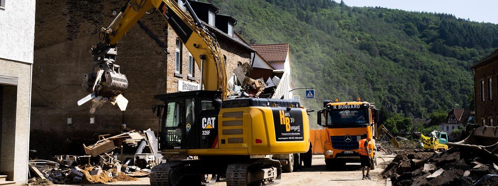 Rheinland-Pfalz, Ahrbrück: Ein Bagger lädt Schutt auf einen Lastwagen.