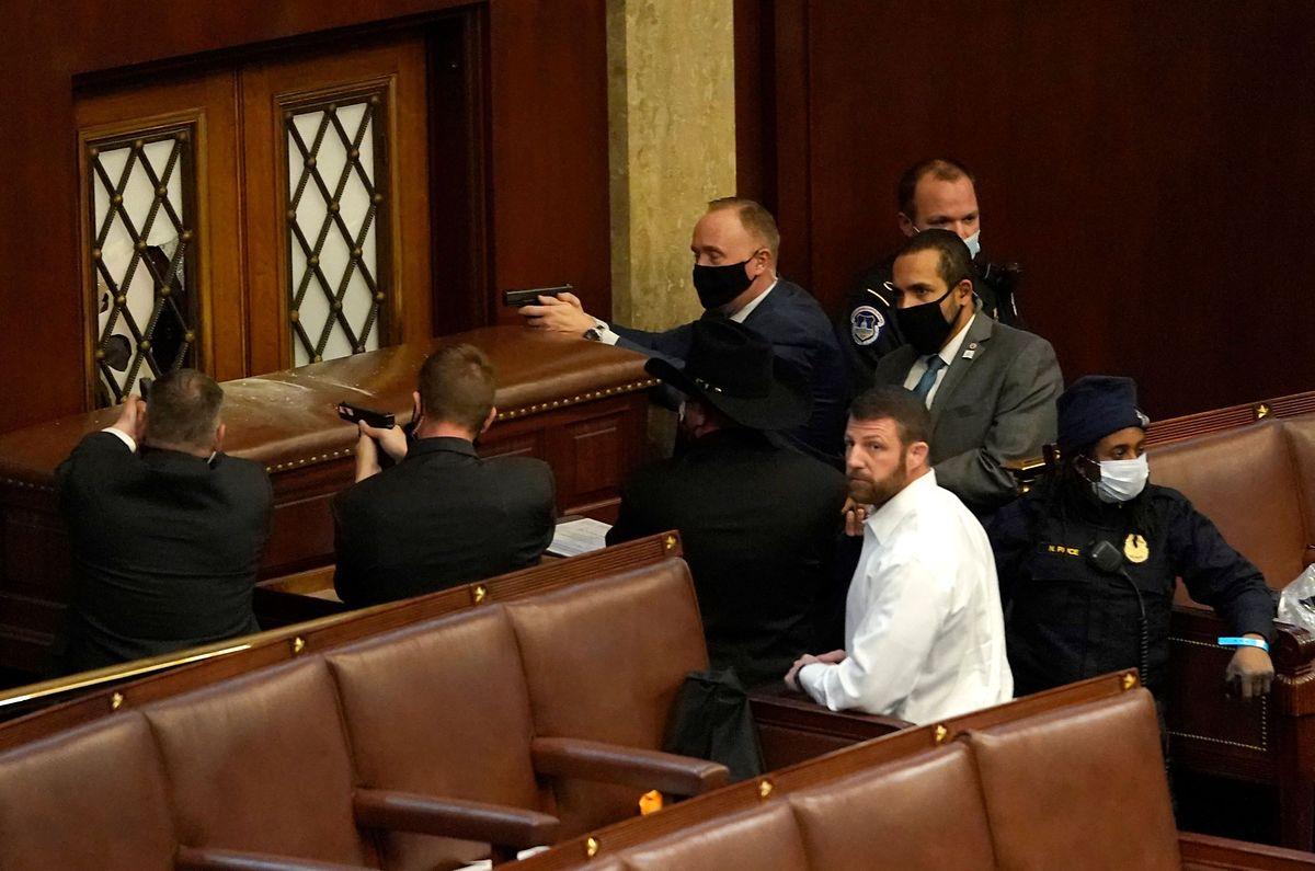 Polizeibeamte versuchen die Kammer des Repräsentantenhauses zu barrikadieren, während Trump-Anhänger gegen die Türen hämmern. Im Bild sind gezogene Schusswaffen zu sehen.