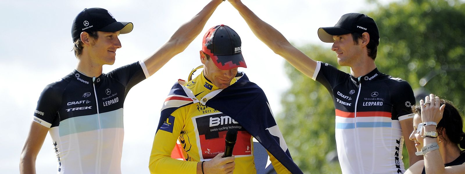 Andy (l.) und Fränk Schleck (r.) beglückwünschen Tour-de-France-Sieger Cadel Evans.